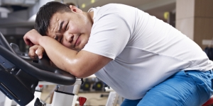an overweight young man exhausted with exercising in fitness center.